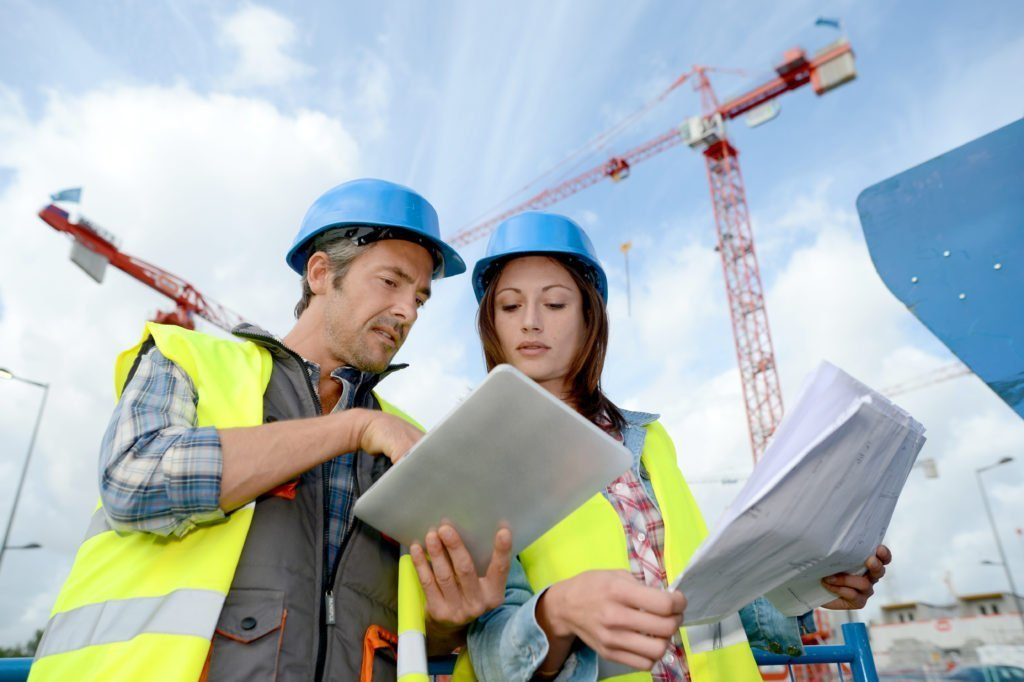 Construction manager and engineer working on building site