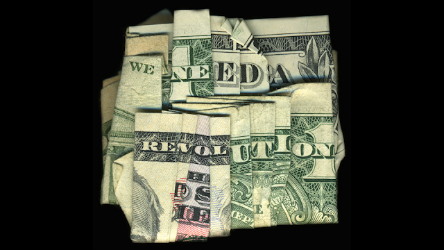 "Dollar bill folded to read ""We need a revolution"" referring to detailing BIM: no lines necessary"
