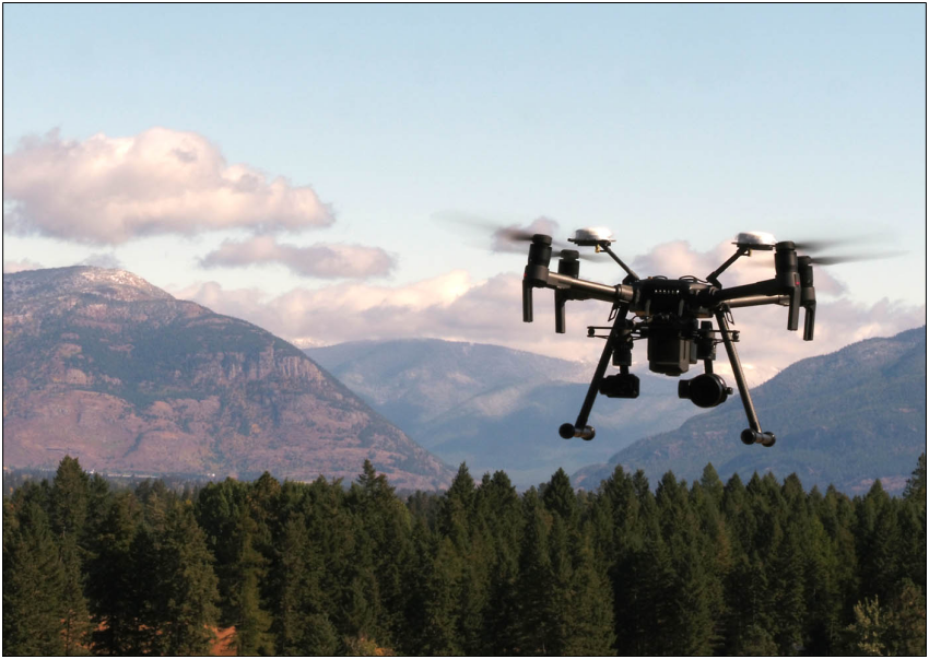 JDI Matrice 200 drone flying above pine trees with mountains in the background