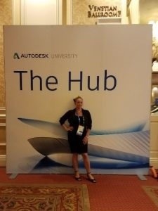 april mccall standing in front of the autodesk university hub banner