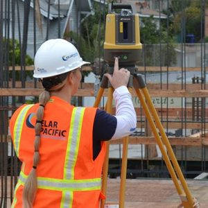 woman setting up a robotic total station on construction site for point layout